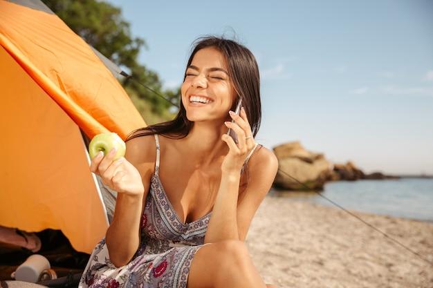 Jonge mooie brunette meid die appel eet en aan de telefoon praat terwijl ze op het strand zit te kamperen