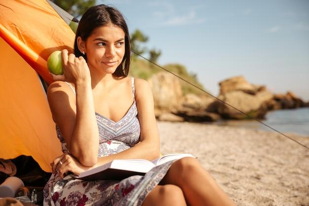 Jonge mooie brunette meid die appel eet en een boek leest terwijl ze op het strand zit te kamperen