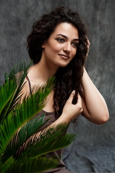 Jonge mooie brunette meisje in tropische planten over grijze muur