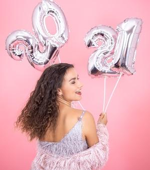 Jonge mooie brunette met krullend haar en een open rug in profiel glimlacht op een roze muur met zilveren ballonnen voor het nieuwe jaarconcept