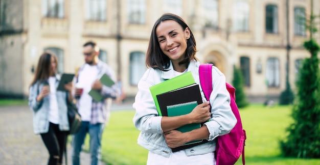Jonge mooie brunette student meisje in denim kleding met rugzak en boeken in handen op een groep van haar studentenvrienden