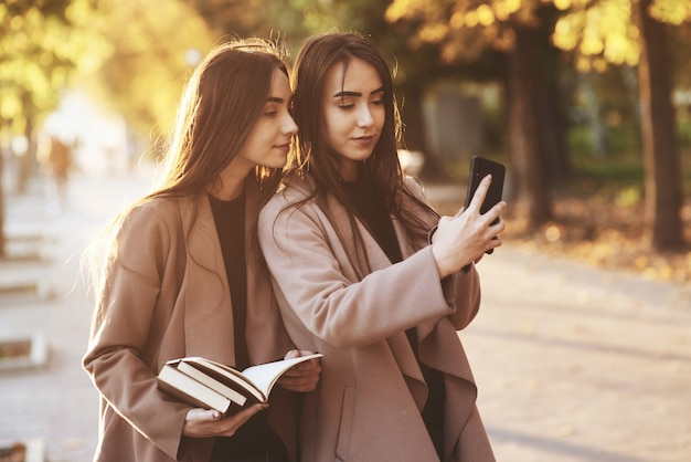 Jonge mooie brunette tweelingmeisjes kijken elkaar aan en nemen selfie met zwarte telefoon, terwijl een van hen boeken vasthoudt, jas draagt, staande op herfst zonnig park steegje op onscherpe achtergrond.