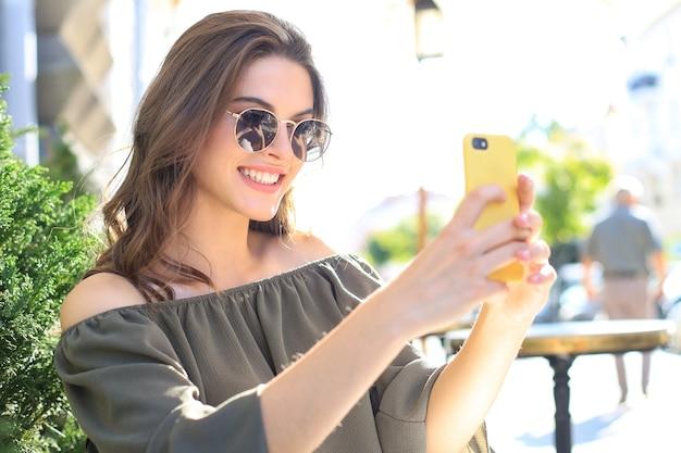 Jonge mooie brunette vrouw buiten in de zomerstad neemt een selfie via de mobiele telefoon.