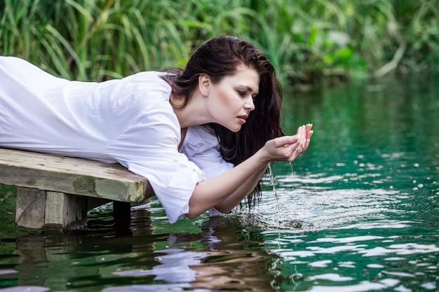 Jonge mooie brunette vrouw geniet van het meer met turkoois helder water