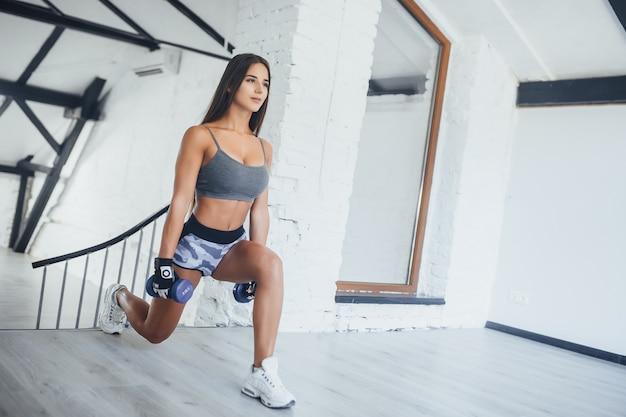 Jonge mooie brunette vrouw hebben oefeningen in de sportschool loft