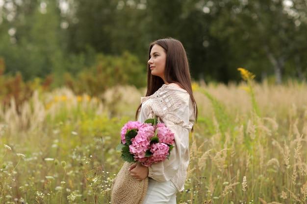 Jonge mooie brunette vrouw houdt boeket van roze bloemen hortensia in een strozak,