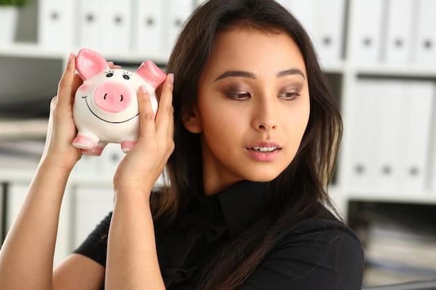 Jonge mooie brunette vrouw houdt spaarvarken in armen