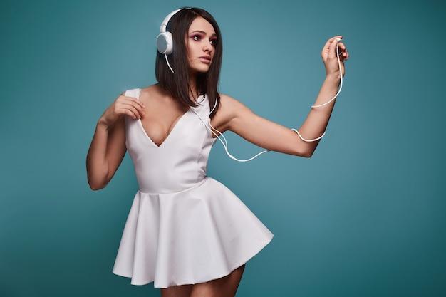 Jonge mooie brunette vrouw in jurk met koptelefoon