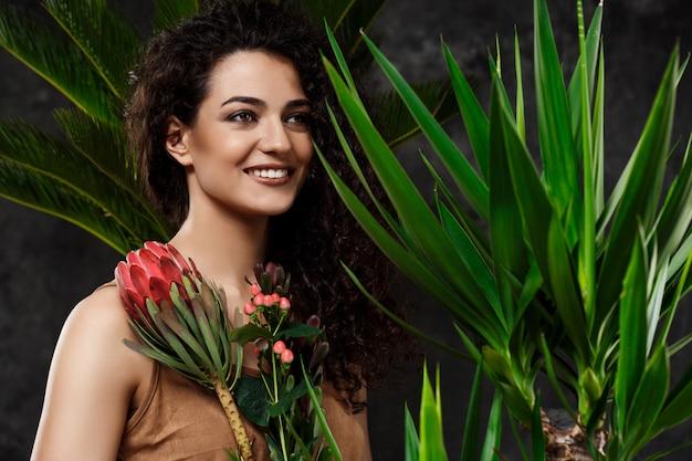 Jonge mooie brunette vrouw in tropische planten over grijze ondergrond