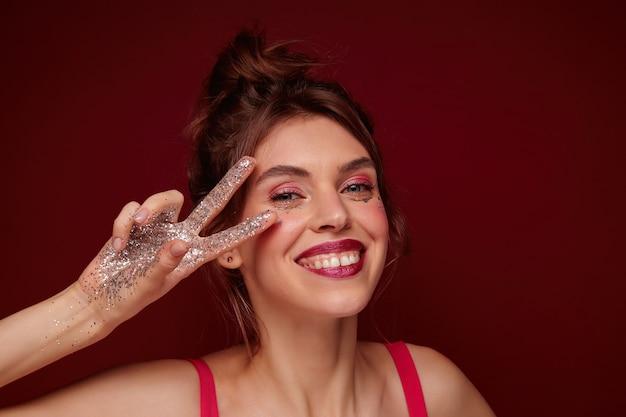 Jonge mooie brunette vrouw met avondmake-up casual kapsel dragen en kijken met charmante glimlach, vredesteken vouwen met opgeheven vingers, geïsoleerd