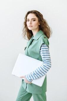 Jonge mooie brunette vrouw met een laptop in haar handen en kijken naar de camera op een witte achtergrond
