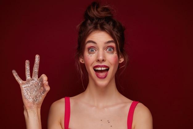 Jonge mooie brunette vrouw met open ogen met knot kapsel en feestelijke make-up kijkt opgewonden en verhoogt ok gebaar met glitters op haar hand, geïsoleerd
