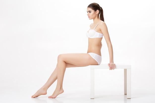 Jonge mooie brunette vrouw met perfect lichaam in wit ondergoed
