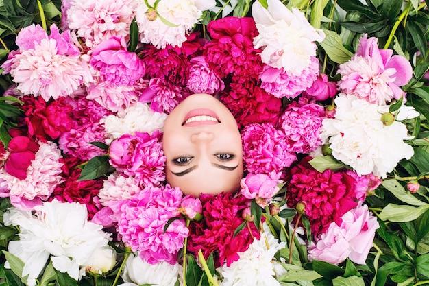 Jonge mooie brunette vrouw model met mooie make-up en lang haar in roze kleuren - pioenrozen