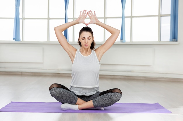Jonge mooie brunette vrouw praktijken yoga in de hal.