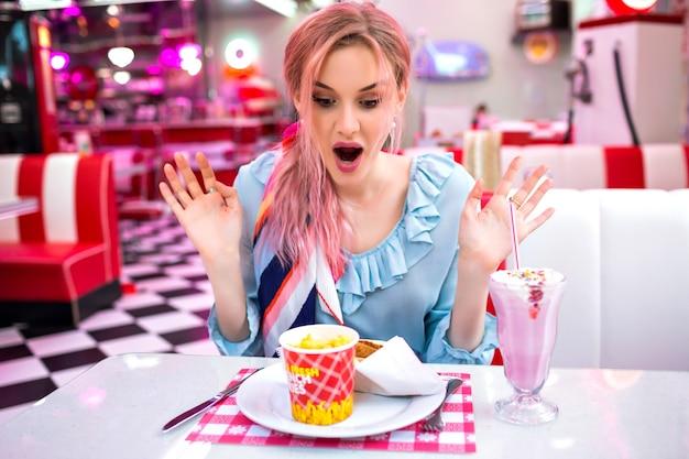 Jonge mooie charmante vrouw met ongebruikelijke roze haarkleuren, zittend op vintage amerikaans café, expressieve positieve verrast emoties, pastel vintage kleding en accessoires, geniet van haar fastfoodmaaltijd