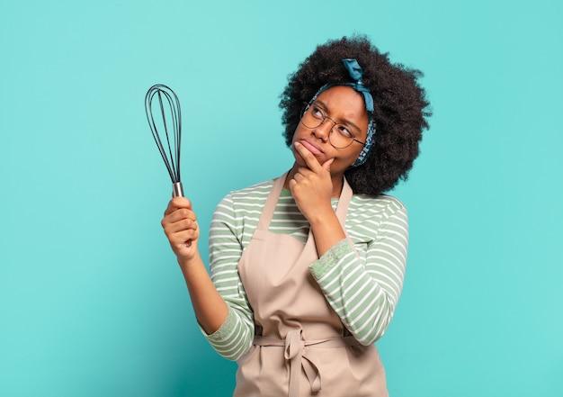 Jonge mooie chef-kok van de afrovrouw met een mixer