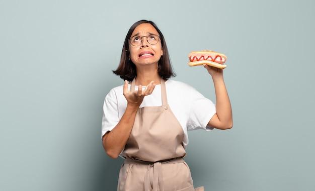 Jonge mooie chef-kokvrouw met hotdog
