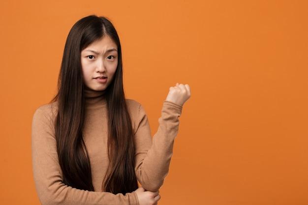 Jonge mooie chinese vrouw aanraken achterkant van het hoofd, denken en het maken van een keuze.