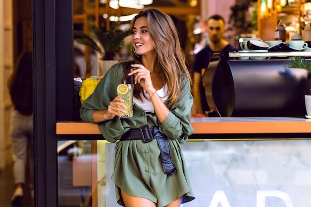 Jonge mooie dame die geniet van vrije tijd in stadscafetaria en bar, citroen drinkt en leuke, trendy hipsteroutfit heeft, afgezwakte kleuren.