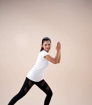 Jonge mooie dame die sportkleding draagt, staande voeten uit elkaar knielt, handen omhoog naast haar gezicht, beetje gedraaid, danstraining om te oefenen, met een gelukkig gevoel