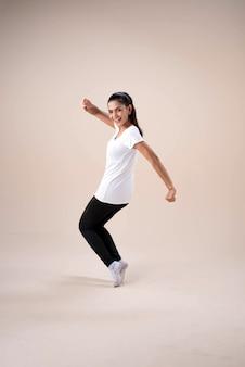 Jonge mooie dame die sportkleding draagt, staande voeten uit elkaar knielt, stapt, vuisten op en neer een beetje gedraaid opheft, danstraining voor oefening, met een gelukkig gevoel