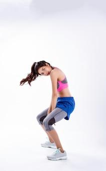 Jonge mooie dame die sportwear draagt, voeten uit elkaar houdt, knielt en bewegend lichaam, danstraining voor oefening, met gelukkig gevoel