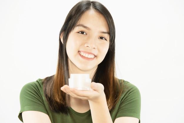 Jonge mooie dame die vochtinbrengende crèmeroom voor de zorg van de gezichtshuid gebruiken - vrouw en kosmetisch de schoonheidsverzorging van de make-upgezicht het concept van de huidzorg