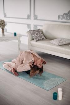 Jonge mooie dame doet asana thuis op yogamat