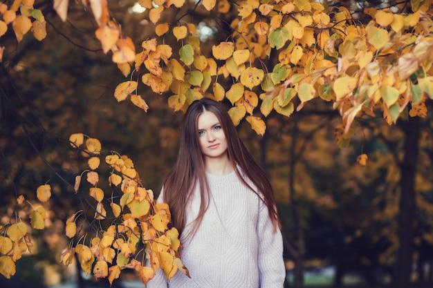 Jonge mooie dame in de herfstbladeren