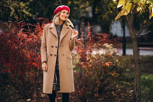 Jonge mooie dame in een rode barret buiten in park