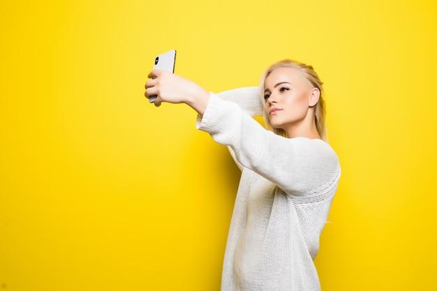 Jonge mooie dame meisje in witte trui maakt selfie op haar smartphone op geel