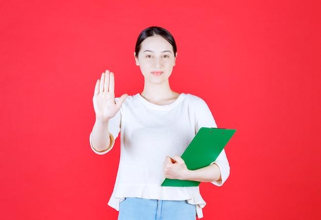 Jonge mooie dame met klembord en gebaren stop