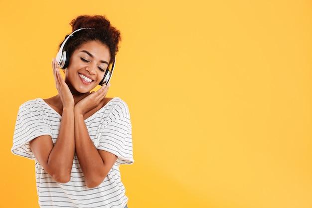 Jonge mooie dame met krullend haar het luisteren geïsoleerde muziek