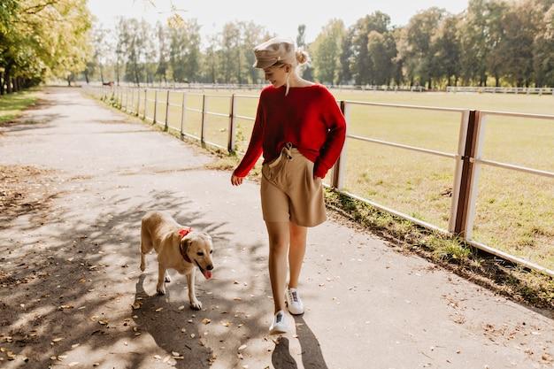 Jonge mooie dame speelt met haar hond in het park. mooie blonde en witte labrador die samen een goede tijd hebben.