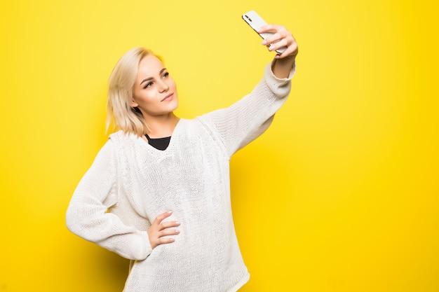 Jonge mooie dame vrouw meisje in witte trui maakt selfie op haar smartphone op geel