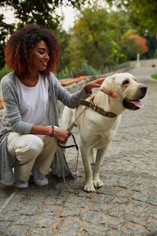 Jonge mooie dame zitten met vriendelijke hond in park