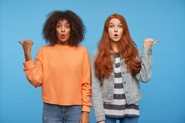 Jonge mooie dames met open ogen die in verschillende richtingen met duimen tonen en verbaasd met opgetrokken wenkbrauwen kijken, poseren over blauwe muur