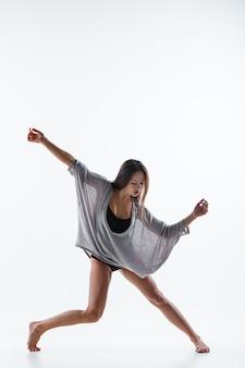 Jonge mooie danser in beige jurk dansen op witte achtergrond