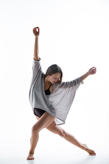 Jonge mooie danser in beige jurk dansen op witte muur