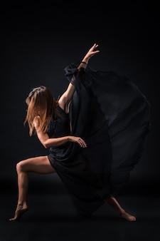Jonge mooie danser in beige jurk dansen op zwart