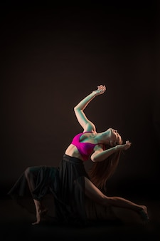 Jonge mooie danser in beige jurk dansen op zwarte muur
