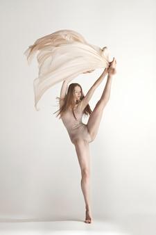 Jonge mooie danser in beige zwembroek dansen op grijs