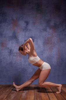 Jonge mooie danseres in beige badmode dansen op lila op houten vloer