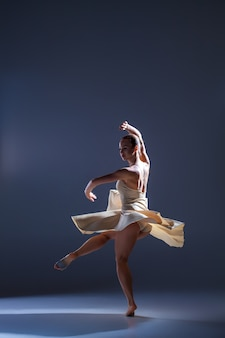 Jonge mooie danseres in beige jurk dansen op grijze studio achtergrond