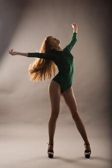 Jonge mooie danseres poseren in een studio op grijze achtergrond
