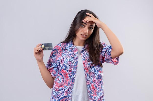 Jonge mooie de holdingscreditcard die van de reizigersvrouw verward wat betreft hoofd, twijfelachtige uitdrukking over witte muur kijken