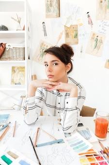 Jonge mooie de manierzitting van de vrouwenmanier bij haar bureau