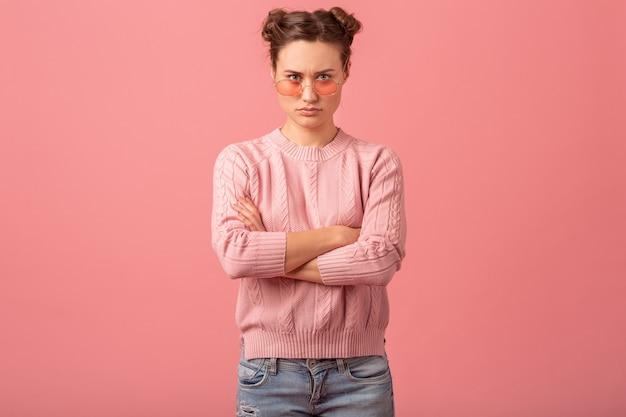 Jonge mooie denkende vrouw die een probleem heeft, neerkijkt in roze sweater en zonnebril die op roze studioachtergrond wordt geïsoleerd