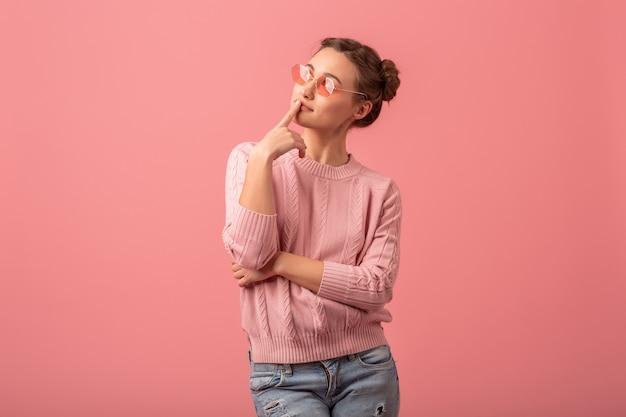 Jonge mooie denkende vrouw die omhoog in roze sweater en zonnebril kijkt die op roze studioachtergrond wordt geïsoleerd